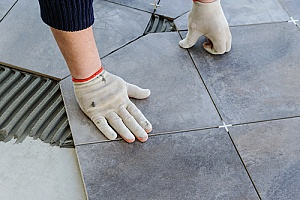 a contractor laying tile during a Northern Virginia bathroom remodel