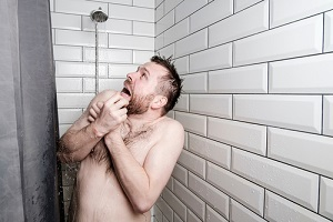 man shocking look at cold water shower