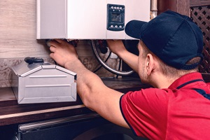 a young skilled worker regulates the gas boiler before use